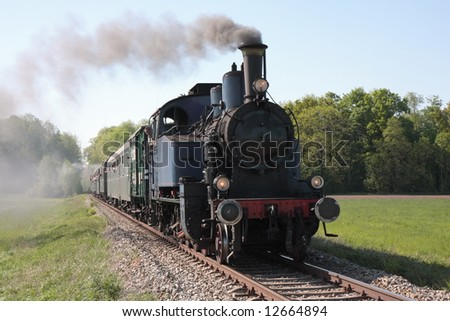 old steam engine powered train approaching - stock photo