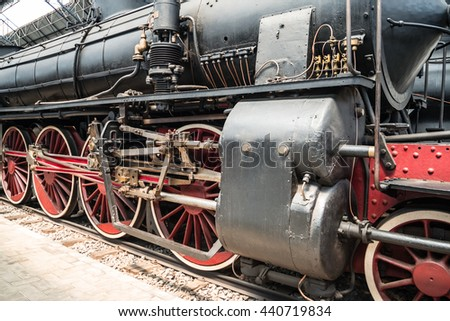 Old steam locomotive standing on the platform of the station - stock photo