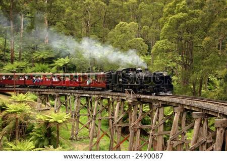 Old steam train crossing a bridge - stock photo