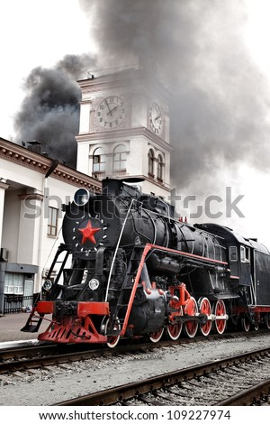 Old steam train is leaving a station. Vintage Steam engine locomotive train moving down railroad track towards camera.