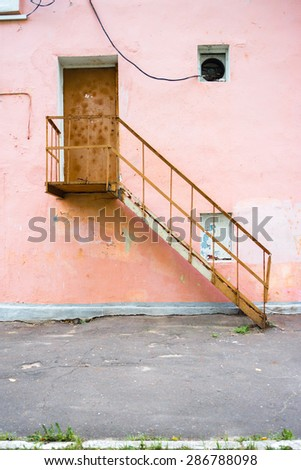 Old steel doors in a building with a pink wall