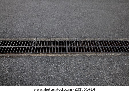 Old steel drainage of the asphalt road. - stock photo