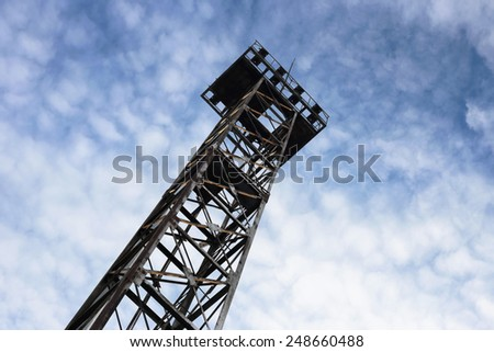 old steel tower on a background of clouds - stock photo