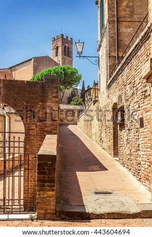 Old stone alley in sunny day in Siena, Tuscany, Italy. - stock photo