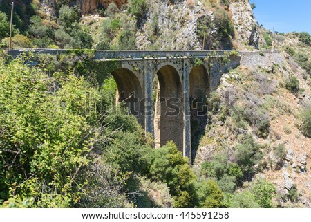 Old stone arch bridge on the old road to Rethymno.  The route leads along a beautiful landscape from south to the north of Crete - stock photo