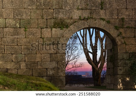old stone arch door in a wall and a far tree at sunset - stock photo