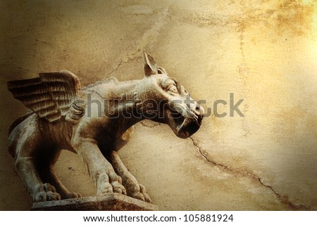 Old stone background with a mythical winged dog sculpture - stock photo