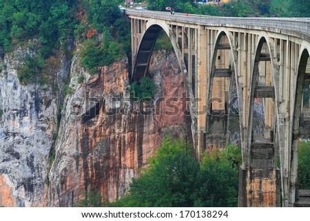 Old stone bridge arches span across deep canyon - stock photo