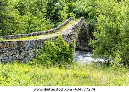 Old Stone bridge over beautiful river in summer - Pyrenees. Andorra la Vella. Andorra. - stock photo