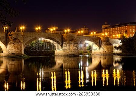 old stone bridge through the river Ebro in Zaragoza with night illumination, Spain - stock photo