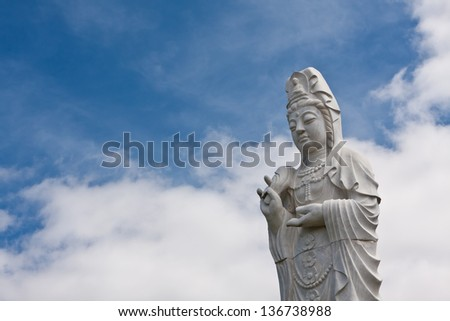Old stone buddha statue, good for travel and religious themes with beautiful blue sky.