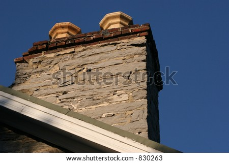 Old stone chimney against blue sky. - stock photo