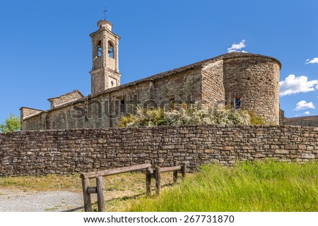 Old stone church under blue sky in town of Prunetto, Italy. - stock photo