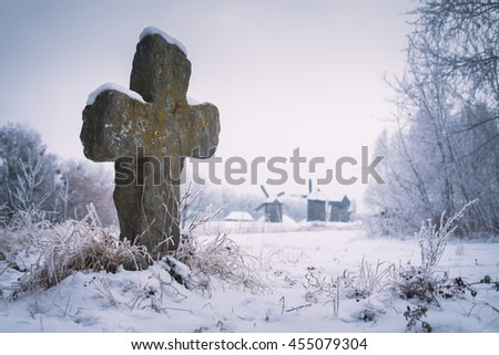 Old stone cross. Burial at the Museum of Folk Architecture and way of life Ukrainians. Winter landscape. Pirogovo museum, Kiev, Ukraine, Europe. Artistic style of photos processing. Color toning - stock photo