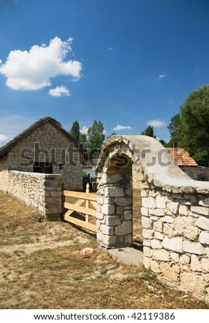 old stone fence with a gate built of limestone - stock photo
