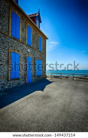 Old stone house with blue shutters at sea side - stock photo