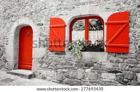 Old stone house with red wooden shutters and red door. Boxes with red and white flowers on the window. Brittany, France. Retro aged photo. - stock photo
