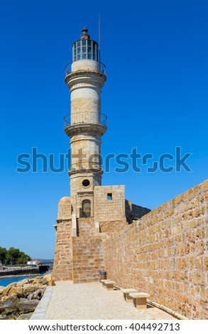 old stone lighthouse against a blue sky, view from below