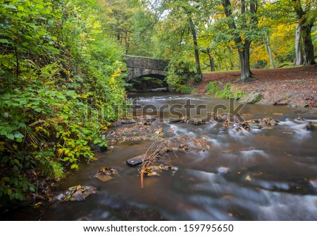 old stone packhorse bridge crossing  a stream in a yorkshire dales woodland beauty spot in autumn - stock photo