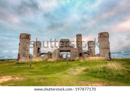 Old stone ruins of a castle, house or manor in medievel France with a dramatic grey and cloudy sky in the background and bright green grass in the foreground./ Old Stone Castle Ruins. - stock photo