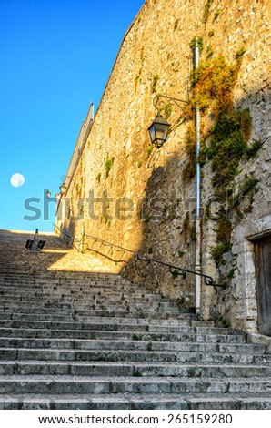 Old stone stairs and a wall on a street in the small city, France. The moon in the distance. - stock photo