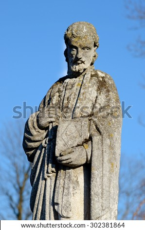 Old stone statue at the tomb of the evangelist in the old cemetery on the background of the sky - stock photo