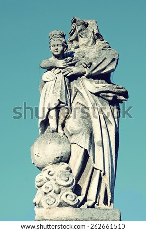 Old stone statue of Jesus and Our Lady of partially destroyed head on the headstone in the cemetery in Ukraine in vintage style - stock photo