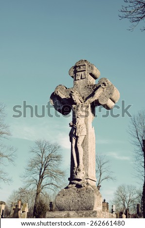 Old stone statue of Jesus crucified on the cross on the tombstone in the cemetery in Ukraine in vintage style - stock photo