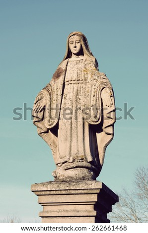 Old stone statue of the Virgin on the tombstone in the cemetery in Ukraine in vintage style - stock photo