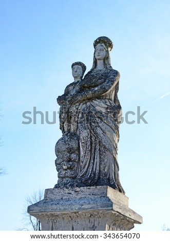 Old stone statue of the Virgin on tomb and Jesus Christ in the cemetery in Ukraine - stock photo