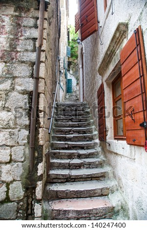 Old stone steps through a narrow alley with red shutters