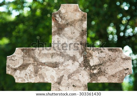 Old stone tumbstone cross on graveyard with lot of copy-space on it for designers