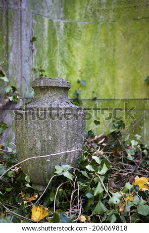 old stone urn in front of a wall - stock photo