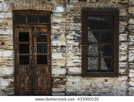 Old stone wall detail with weathered wooden door and window  - stock photo