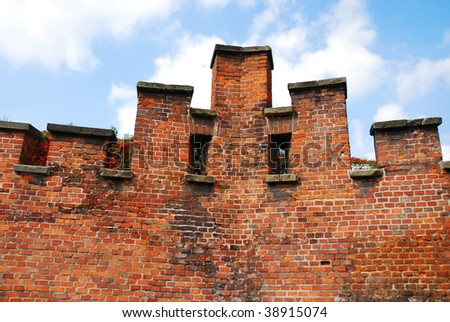 Old stone wall on the blue sky - stock photo