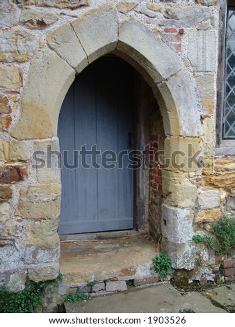 Old stone wall with dark wooden doorway - stock photo