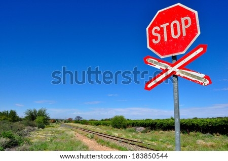 Old stop railway crossing sign by the railway tracks against the blue sky - stock photo