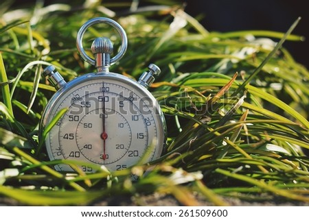 Old stopwatch in green grass - stock photo