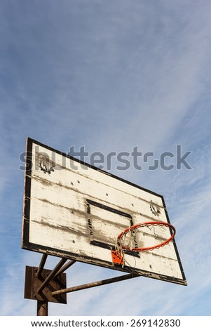 Old street basketball basket with a cloudy blue sky - stock photo