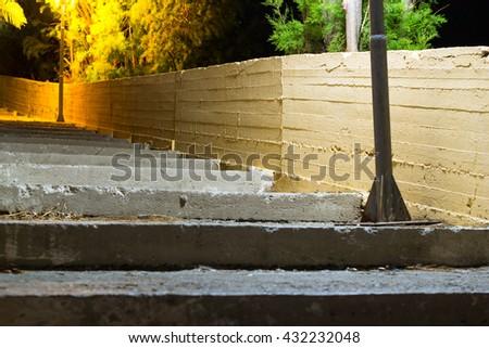 Old street concrete stairs, illuminated by road lights. Dark quiet lonely night in resort mediterranean village. Bali, Rethymno, Crete, Greece - stock photo