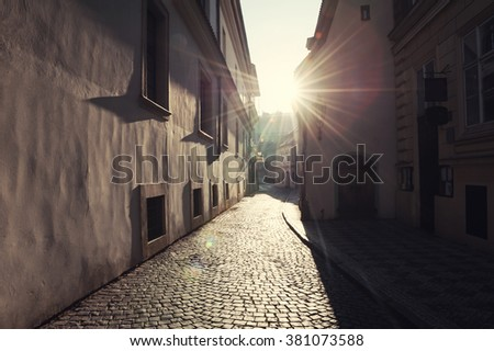 Old street in Prague at morning sunlight. Vintage filter - stock photo
