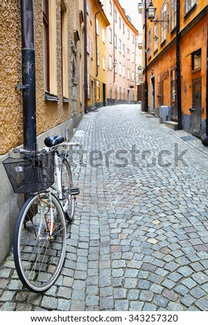 Old street in Stockholm, Sweden. Shallow DOF, focus on the bike - stock photo