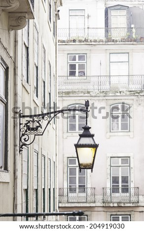 Old street lamp on a classical facade in Lisbon, detail of an old lighting in the city, Art and Tourism - stock photo
