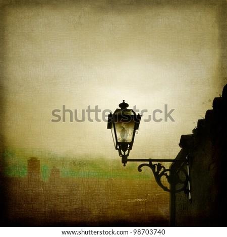 Old street lamp on foggy city skyline - stock photo