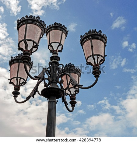 Old street lamps against the blue sky with clouds - stock photo
