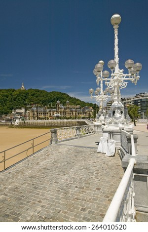 Old street lights are seen on Paseo del Muelle, a walkway along the harbor of Playa de La Concha, in Donostia-San Sebastian, Basque region of Spain, the Queen of Euskadi's and Cantabrian Coast - stock photo
