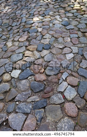 Old street pavement, made of granite stone pieces.