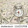 old style alarm clock and on dollars background - stock photo