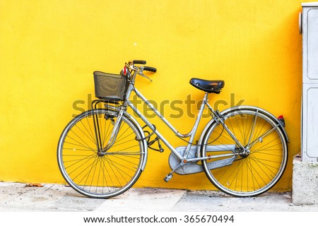 Old style bicycle parked against yellow wall. - stock photo
