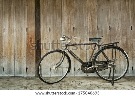 old style black bicycle and wooden door
